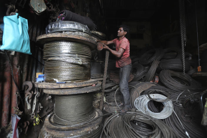 A man works in an iron and steel scrap workshop in Mumbai, India, Friday, June 11, 2021. India's economy was on the cusp of recovery from the first pandemic shock when a new wave of infections swept the country, infecting millions, killing hundreds of thousands and forcing many people to stay home. Cases are now tapering off, but prospects for many Indians are drastically worse as salaried jobs vanish, incomes shrink and inequality is rising. (AP Photo/Rafiq Maqbool)