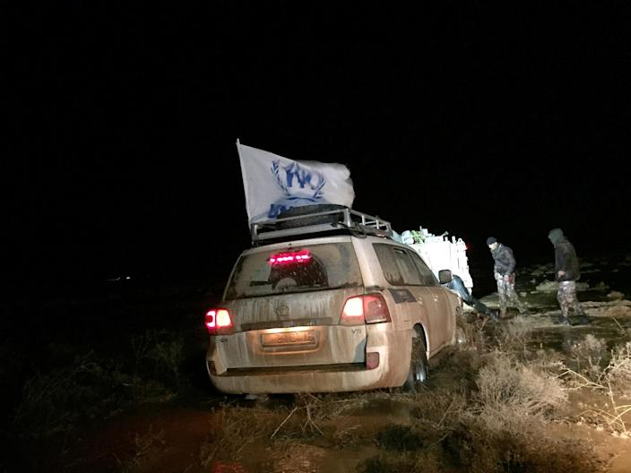 In this Wednesday, March 1, 2017 photo, Jordanian border guards using armored personnel carriers try to pull U.N. cars that are stuck in a flooded area in the remote desert along the Jordan-Syria border. U.N. agencies are ramping up aid delivery to tens of thousands of war-displaced Syrians stuck in the desert on Jordan's sealed border, after months of being denied access. Yet harsh weather and anxious crowds often disrupt one of the U.N.'s most complex missions anywhere. (AP Photo/Karin Laub)