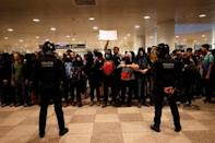 Police officers stand guard as protesters demonstrate at the airport, in Barcelona
