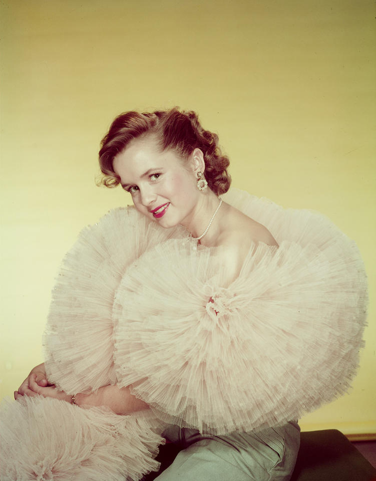 """<p>Reynolds was discovered by a Warner Bros. film scout and made her movie debut in 1948 in """"June Bride."""" This called for a giant boa, naturally. (Photo: Getty Images) </p>"""