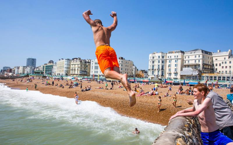 Children can be seen jumping of the pontoon in the sea in Brighton and Hove - LNP
