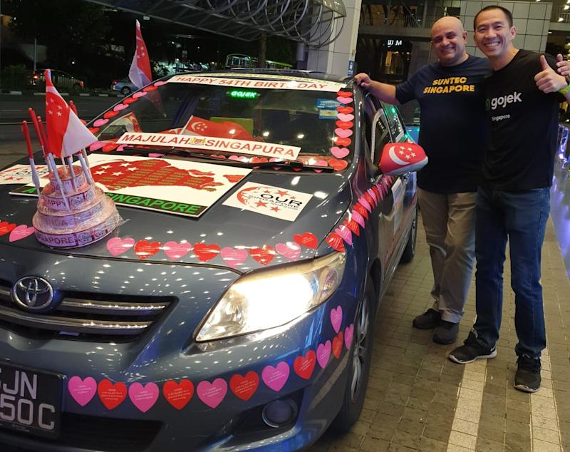 Gojek Singapore GM Lien Choong Luen (right) with Arun Madhok (left), CEO of Suntec Singapore International Convention & Exhibition Services posing with a car owned by Gojek driver, Henry Ho. (PHOTO: Gojek)