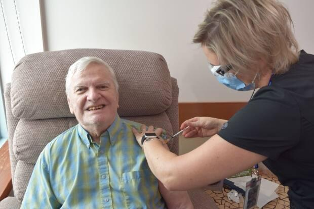 Resident Gilles Charest gets a COVID-19 vaccine dose at Ottawa's Perley and Rideau Veterans' Health Centre in January 2021 when long-term care home residents were receiving their first doses. (Andréa Fabricius/Perley and Rideau Veterans' Health Centre - image credit)