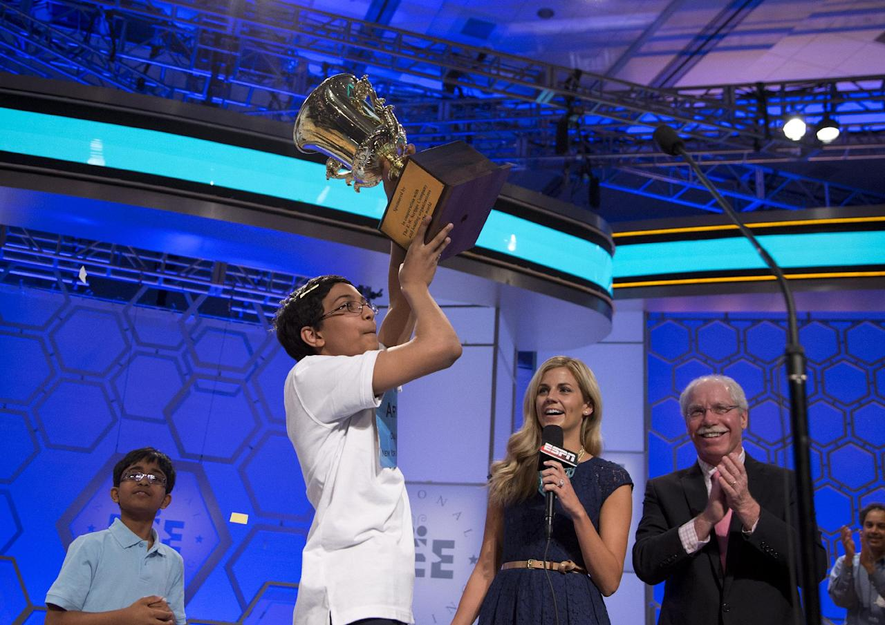"Arvind Mahankali, 13, of Bayside Hills, N.Y., lifts the championship trophy after he won the National Spelling Bee by spelling the word ""knaidel"" correctly on Thursday, May 30, 2013, in Oxon Hill, Md. (AP Photo/Evan Vucci)"