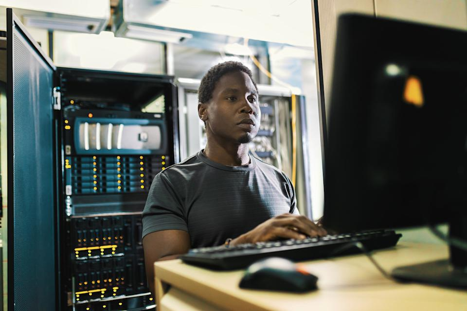 Black man is working in data center with laptop