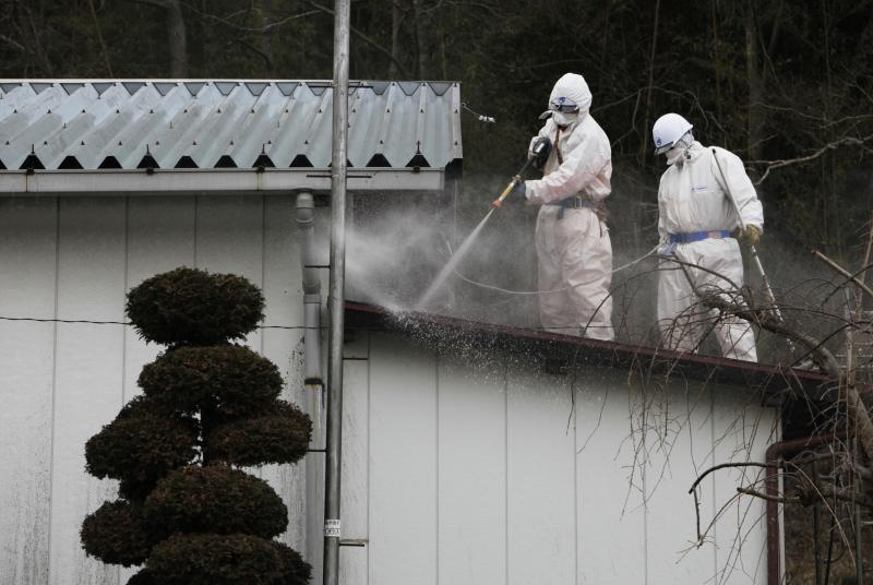 In this photo taken Tuesday, Feb. 21, 2012, workers spray the roof of a radiation-contaminated warehouse in Fukushima, Japan. A massive cleanup has begun in towns contaminated by radiation leaks from the Fukushima Dai-ichi nuclear plant, but experts leading the government-funded projects say there is no successful example they can follow, and they don't know how to judge the effectiveness of a process that is expected to last for years or even decades. (AP Photo/Greg Baker)