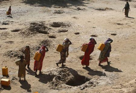 Women carry jerry cans of water from shallow wells dug from the sand along the Shabelle River bed, which is dry due to drought in Somalia's Shabelle region, March 19, 2016. REUTERS/Feisal Omar/File Photo
