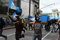 Demonstrators confront riot police during a protest demanding the resignation of Guatemalan President Alejandro Giammattei, in Guatemala City on November 21, 2020