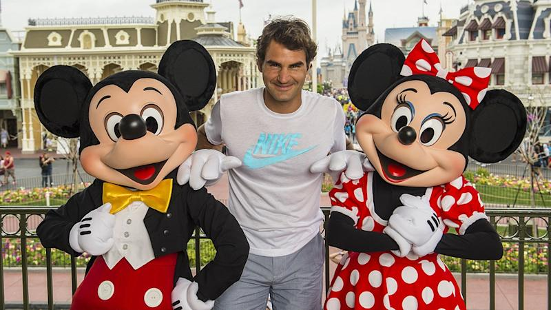 LAKE BUENA VISTA, FL - MARCH 17: In this handout photo provided by Diseny Parks, tennis legend Roger Federer poses with Mickey and Minnie Mouse at the Magic Kingdom park March 17, 2014 in Lake Buena Vista, Florida. The Swiss-born Federer holds the men's world record for most Grand Slam tournaments won, 17, and has spent 302 weeks as the world's number-one ranked male tennis player. (Photo by Matt Stroshane/Disney Parks via Getty Images)