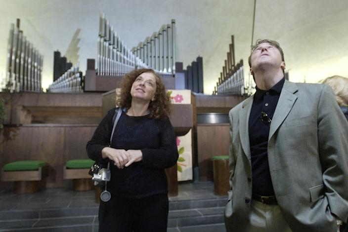 Two people, organ pipes jutting up at various angles behind them, admire the interior of Columbus' North Christian Church.