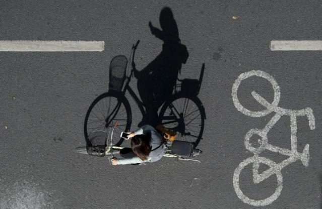 A woman uses her mobile phone while riding her bike on a street in Beijing, China (AFP Photo/NOEL CELIS)