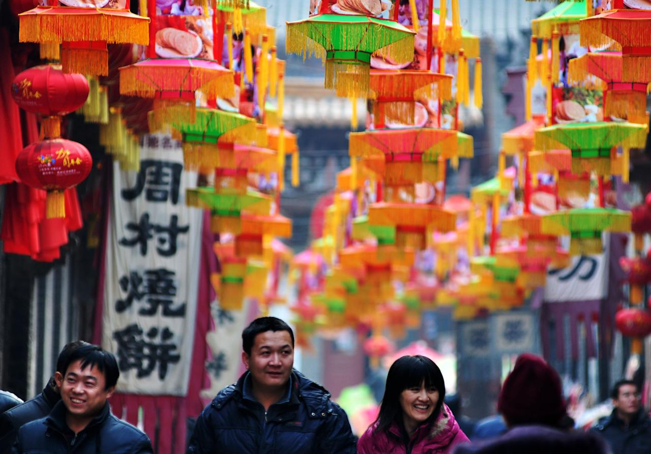 ZIBO, CHINA - JANUARY 08:  (CHINA OUT) People walk under red lanterns on January 8, 2012 in Zibo, China. The new year in the Chinese calendar is the year of Dragon which will fall on January 21, 2012.  (Photo by ChinaFotoPress/ChinaFotoPress via Getty Images)