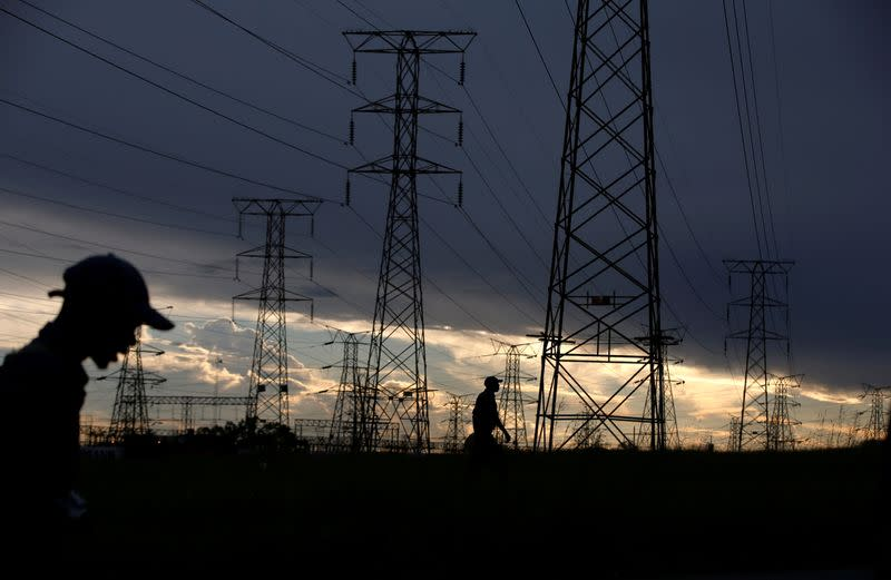 FILE PHOTO: Men walk past electricity pylons as they return from work in Orlando