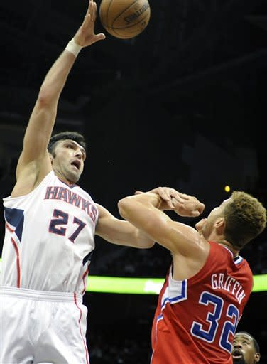 Atlanta Hawks' Zaza Pachulia (27) goes to the basket over Los Angeles Clippers' Blake Griffin in the first half of an NBA basketball game at Philips Arena in Atlanta, Saturday, Nov. 24, 2012. (AP Photo/David Tulis)