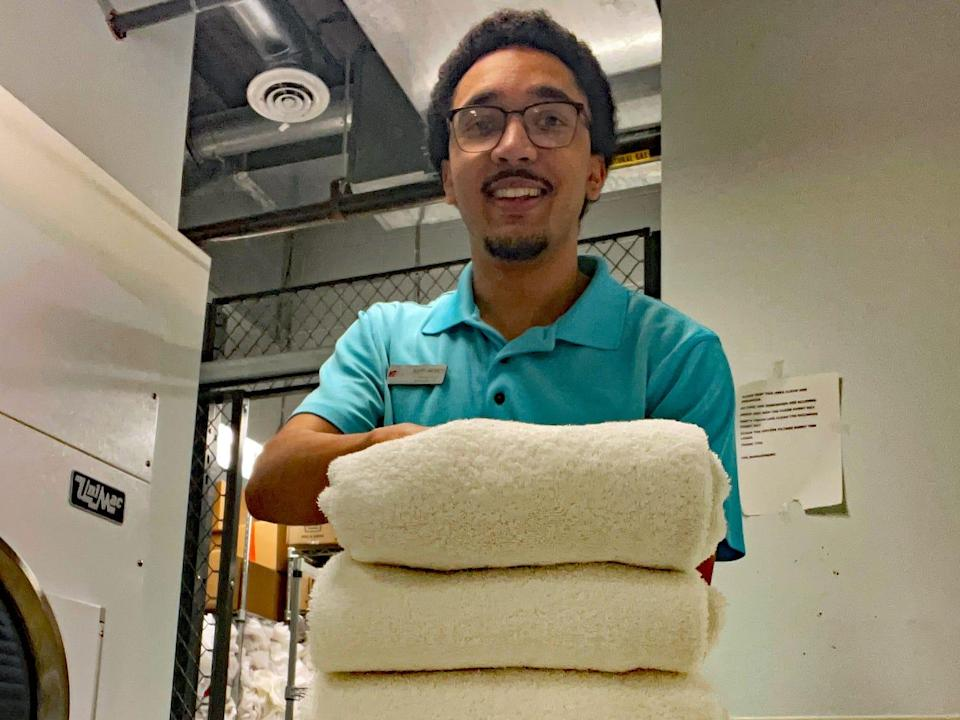 justin offering a stack of towels in the hotel laundry room