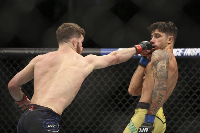 Dustin Ortiz, left, lands a right on Alexandre Pantoja during a mixed martial arts bout at UFC 220, Saturday, Jan. 20, 2018, in Boston. Ortiz won via decision. (AP Photo/Gregory Payan)
