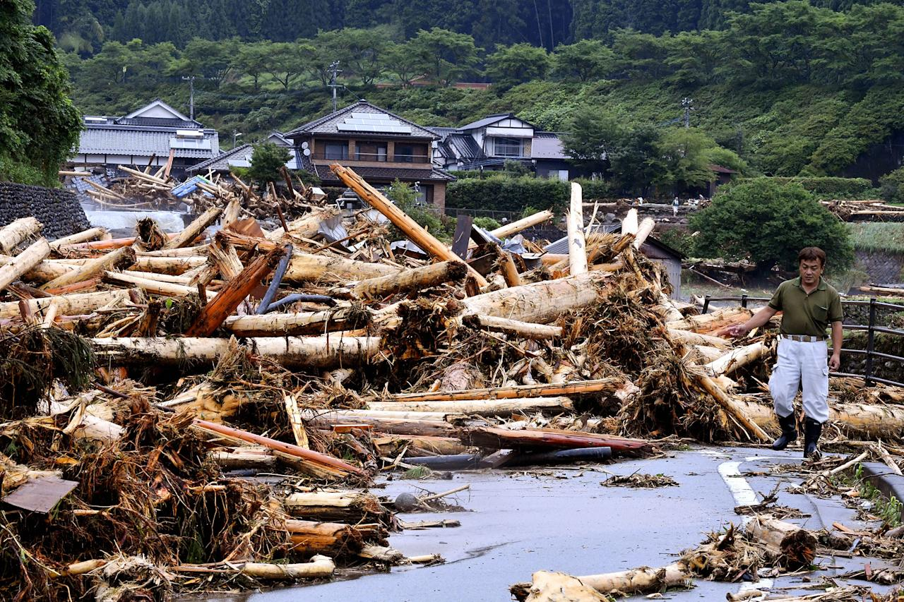 <p>A man trying to return his home gives up as driftwood block the way as torrential rain hit on July 6, 2017 in Toho, Fukuoka, Japan. (Photo: The Asahi Shimbun via Getty Images) </p>