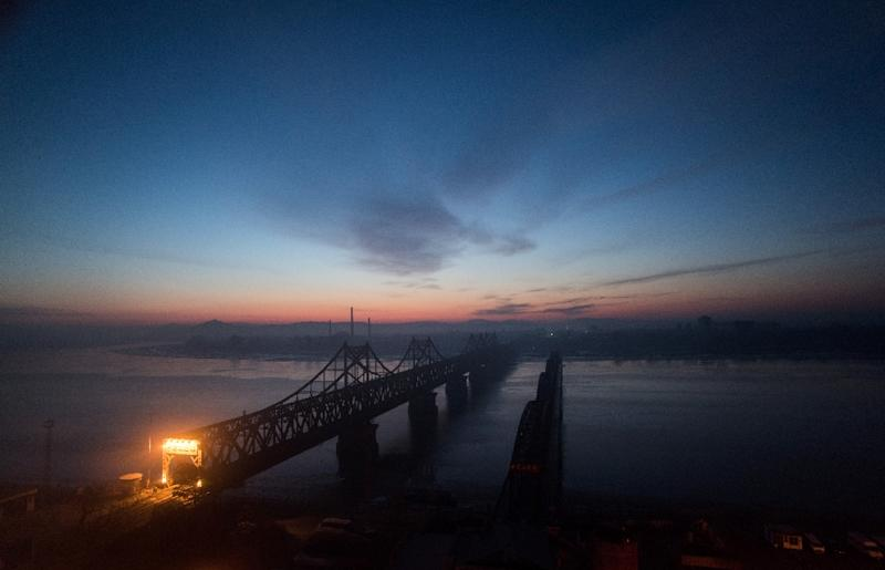The sun rises over the Yalu river in the Chinese border town of Dandong, opposite the North Korean town of Sinuiju (AFP Photo/Johannes Eisele)