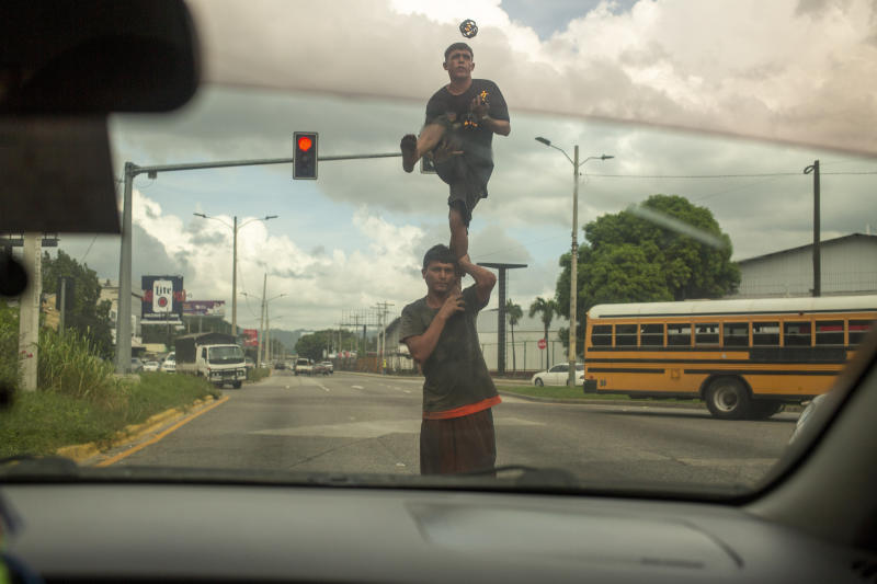 Two street jugglers perform on a corner for money in San Pedro Sula, Honduras on Nov. 28, 2019. The city's criminal life is dominated by two street gangs formed decades earlier in Latino enclaves of Los Angeles, spreading southward as gang members were deported. Today, MS-13 and Mara 18 are the most powerful and feared gangs in Central America, and have operations that reach from Mexico to the U.S. to Europe. (AP Photo/Moises Castillo)