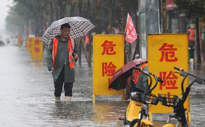 """Workers set up warning signs with the words """"Danger!"""" at a waterlogged area in Wuzhi County in central China's Henan province - Feng Xiaomin/Xinhua"""