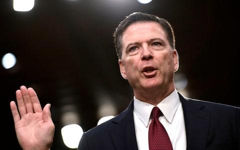 James Comey takes the oath before he testifies during a US Senate Select Committee - Credit: AFP