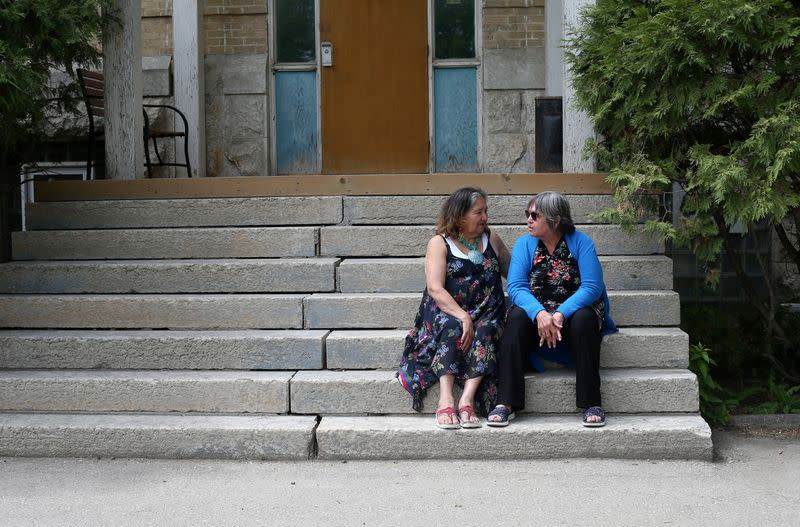 Daniels and Roulette talk on the steps of the former Portage La Prairie Indian Residential School in Canada