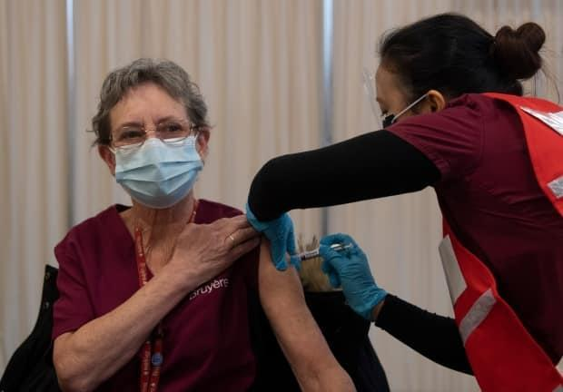 Personal support worker Johanne Lamesse receives the Pfizer-BioNTech COVID-19 vaccine at The Ottawa Hospital on Dec. 15, 2020. The booking system is now up and running for Ottawa's public vaccine clinics, which open later this week. (Adrian Wyld/Canadian Press - image credit)