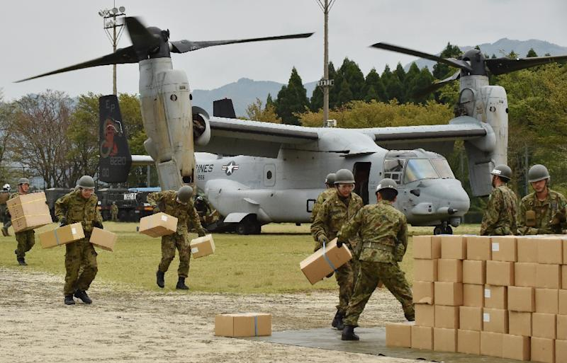 Japanese troops carry emergency aid supplies from a US Marine tilt-rotor Osprey aircraft as part of relief efforts in Kumamoto prefecture on April 18, 2016 (AFP Photo/Kazuhiro Nogi)