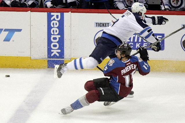 Winnipeg Jets' Mark Stuart (5) lays out Colorado Avalanche's P.A. Parenteau (15) during the first period of an NHL hockey game on Monday, March 10, 2014 in Denver. (AP Photo/Barry Gutierrez)