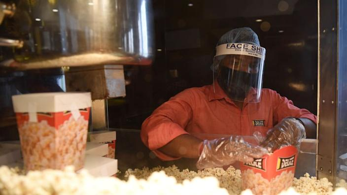 A worker preparing popcorn with health and safety measures after cinemas reopen in India