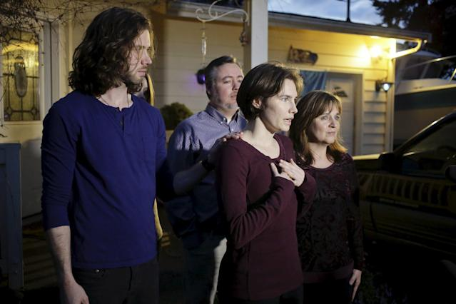 Amanda Knox (2nd R) talks to the press surrounded by family outside her mother's home in Seattle, Washington March 27, 2015. Italy's top court on Friday annulled the conviction of American Amanda Knox for the 2007 murder of British student Meredith Kercher and, in a surprise verdict, acquitted her of the charge. The Court of Cassation threw out the second guilty verdict to have been passed on Knox, 27, and her Italian former boyfriend Raffaele Sollecito for the lethal stabbing. REUTERS/Jason Redmond