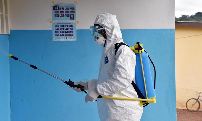 A man wearing a protective suit washes the walls of a health center in Kandopleu village, near Biankouma, on August 14, 2014 (AFP Photo/Issouf Sanogo)