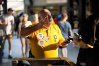 Tom Congdon, center, a vendor at Pittsburgh sports venues for 38 years, mans his beer and water cart in the concourse at PNC Park during a baseball game between the Pittsburgh Pirates and the Atlanta Braves in Pittsburgh, Monday, July 5, 2021. (AP Photo/Gene J. Puskar)