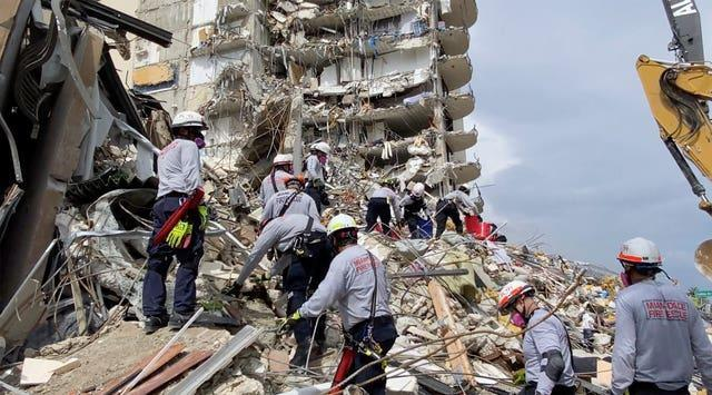 Search and rescue personnel search for survivors through the rubble at the Champlain Towers