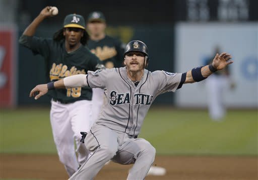 Seattle Mariners' Brendan Ryan, foreground, is chased by Oakland Athletics second baseman Jemile Weeks (19) before being tagged out in a rundown between first and second bases during the fifth inning of a baseball game in Oakland, Calif., Friday, July 6, 2012. (AP Photo/Jeff Chiu)