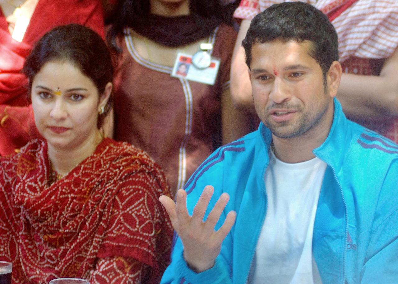 BOMBAY, INDIA:  Indian cricketer Sachin Tendulkar (R) gestures as his wife Anjali (L) looks on during an event organised by the Cancer Patients Aid Association in Bombay, 29 September 2004. During the event Tendulkar spent time talking with child cancer patients and distributing gifts. AFP PHOTO/Sebastian D'SOUZA  (Photo credit should read SEBASTIAN D'SOUZA/AFP/Getty Images)