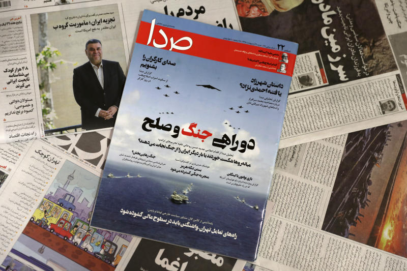 """The front cover of the May 11, 2019 edition of the weekly reformist magazine, Seda, center, is photographed along with other periodicals in Tehran, Iran, May 12, 2019. Iranian authorities shut down Seda that had urged negotiations with the United States, local media reported Sunday. The main headline reads, """"At the crossroads between war and peace."""" (AP Photo/Vahid Salemi)"""