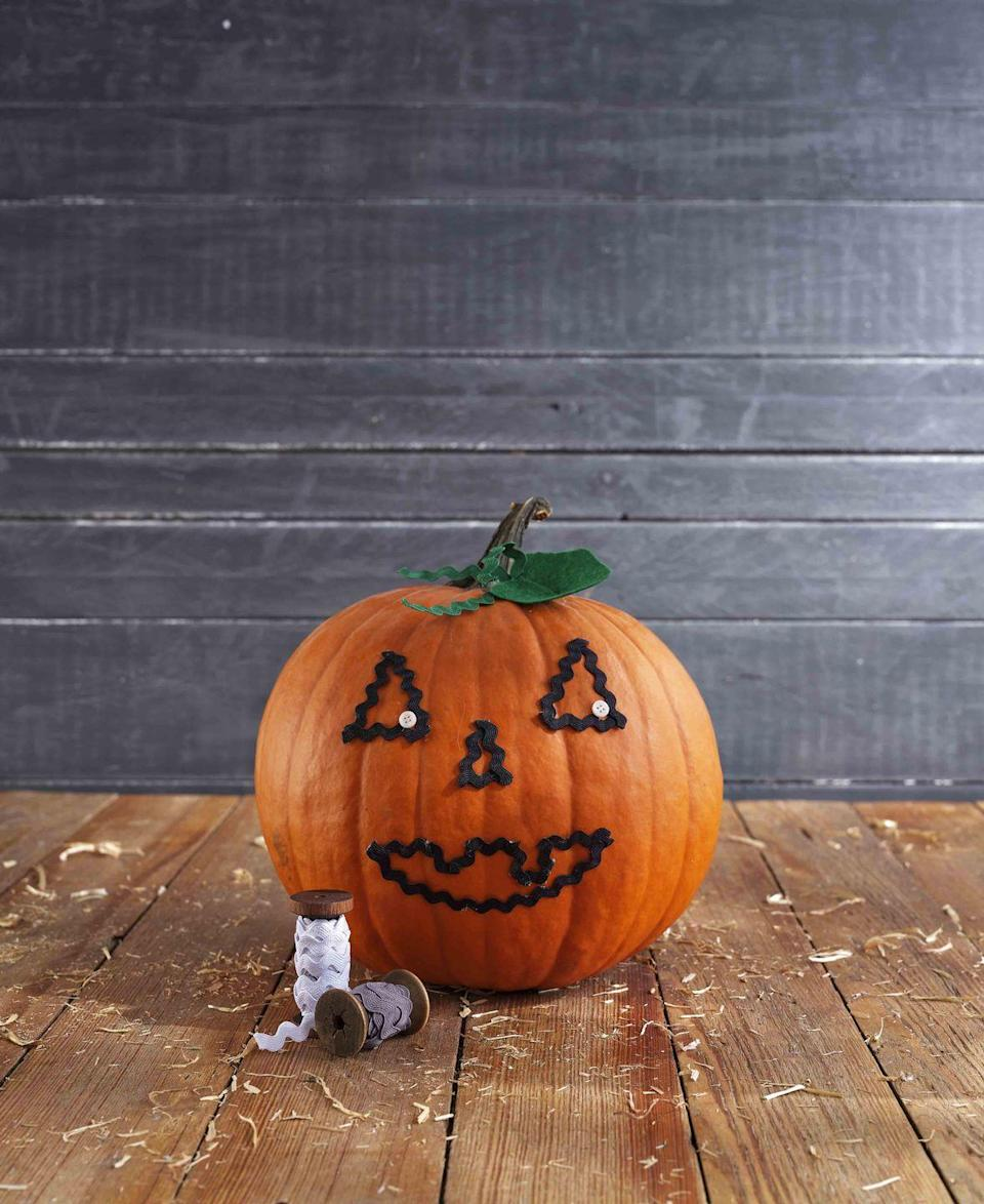 <p>No carving necessary to create this sweet pumpkin face.<strong><br></strong></p><p><strong>Make the pumpkin:</strong> Lightly draw a simple pumpkin face on a pumpkin. Use lengths of black rickrack to cover the drawing, attaching it with hot-glue. Attach small white buttons to the corner of each eye with hot-glue. Cut pumpkin-shaped leaves from green felt and lengths of green rickrack to create tendrils; attach at the base of the pumpkin stem with hot-glue. </p>