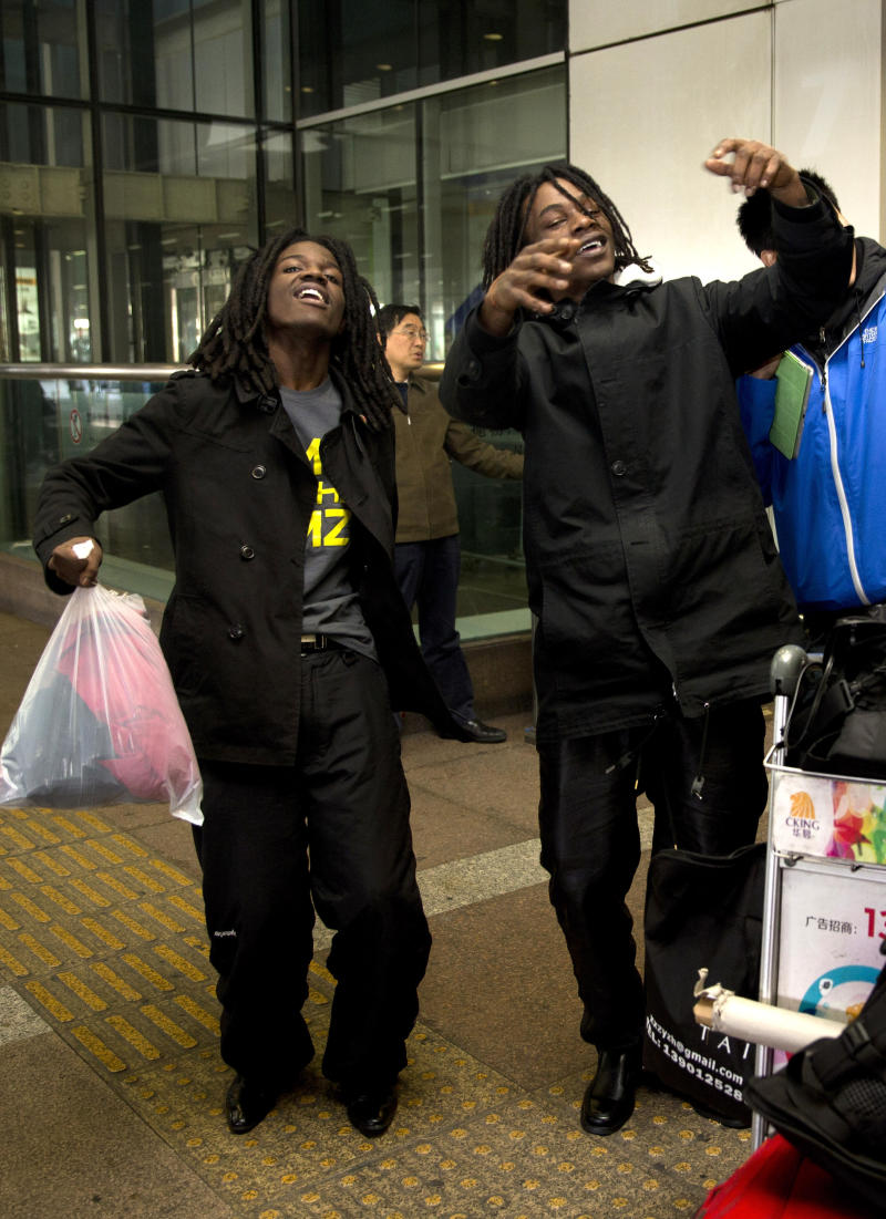 U.S. rappers Pacman, left, and Peso perform a dance at the Beijing Capital Airport in Beijing, after returning from Pyongyang, North Korea Saturday, Nov. 30, 2013. Pacman and Peso, whose real names are Anthony Bobb and Dontray Ennis ended their trip to North Korea on Saturday, after spending five days in North Korea to film their music video, which funded by Kickstarter campaign. (AP Photo/Andy Wong)