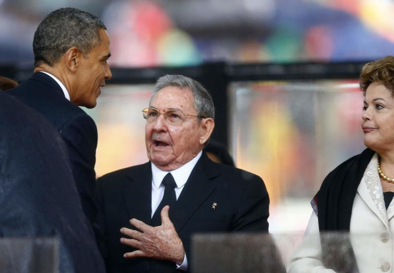 File photo of U.S. President Obama greeting Cuban President Castro at the memorial service for Mandela in Johannesburg