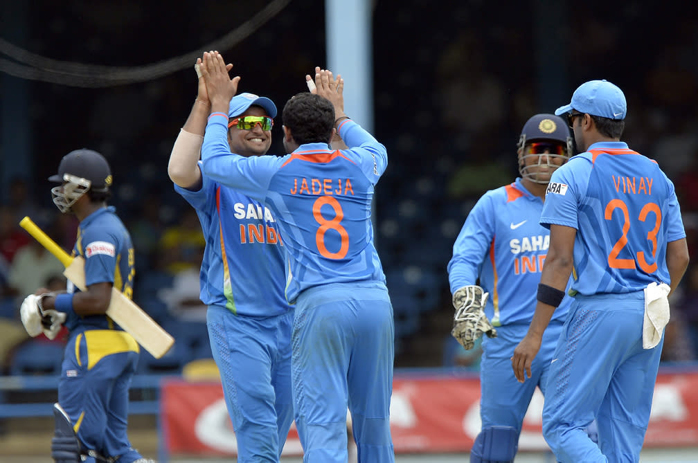 Indian cricketer Ravindra Jadeja (#8) celebrates with teammates after dismissing Sri Lankan Dinesh Chandimal during the final match of the Tri-Nation series between India and Sri Lanka at the Queen's Park Oval stadium in Port of Spain on July 11, 2013. India won the toss and elected to field first. AFP PHOTO/Jewel Samad