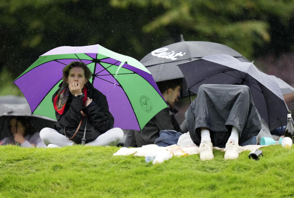 People shelter under umbrellas during a rain delay on day two of the Wimbledon Tennis Championships in London, Tuesday June 29, 2021. (AP Photo/Alberto Pezzali)