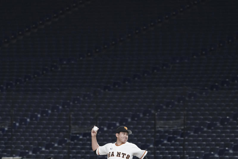 Tomoyuki Sugano of the Yomiuri Giants pitches with a backdrop of empty stands during play in a preseason baseball game between the Yomiuri Giants and the Yakult Swallows at Tokyo Dome in Tokyo Saturday, Feb. 29, 2020. Japan's professional baseball league said Thursday it will play its 72 remaining preseason games in empty stadiums because of the threat of the spreading coronavirus. (AP Photo/Eugene Hoshiko)