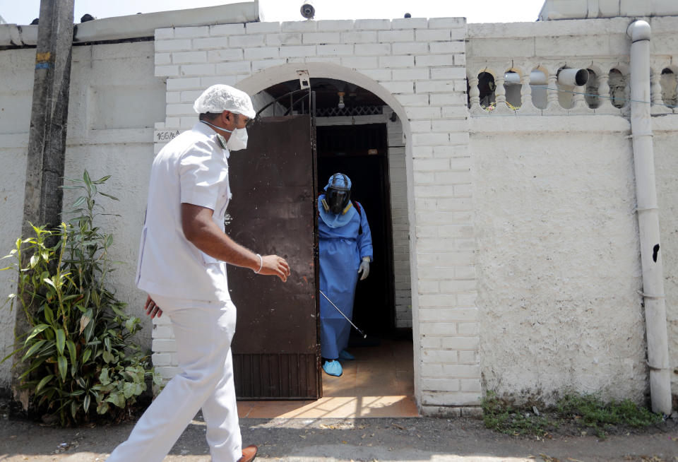 A Sri Lankan health worker sprays disinfectant inside a house in a residential neighborhood where a suspected COVID-19 case was reported in Colombo, Sri Lanka, Saturday, March 14, 2020. For most people, the new coronavirus causes only mild or moderate symptoms. For some, it can cause more severe illness, especially in older adults and people with existing health problems. (AP Photo/Eranga Jayawardena)