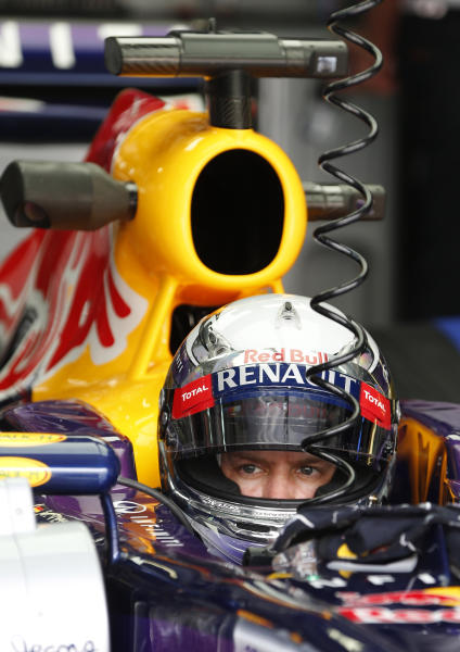 Red Bull driver Sebastian Vettel of Germany waits in his car during the second practice session for Sunday's Malaysian Formula One Grand Prix at Sepang, Malaysia, Friday, March 22, 2013. (AP Photo/Vincent Thian)