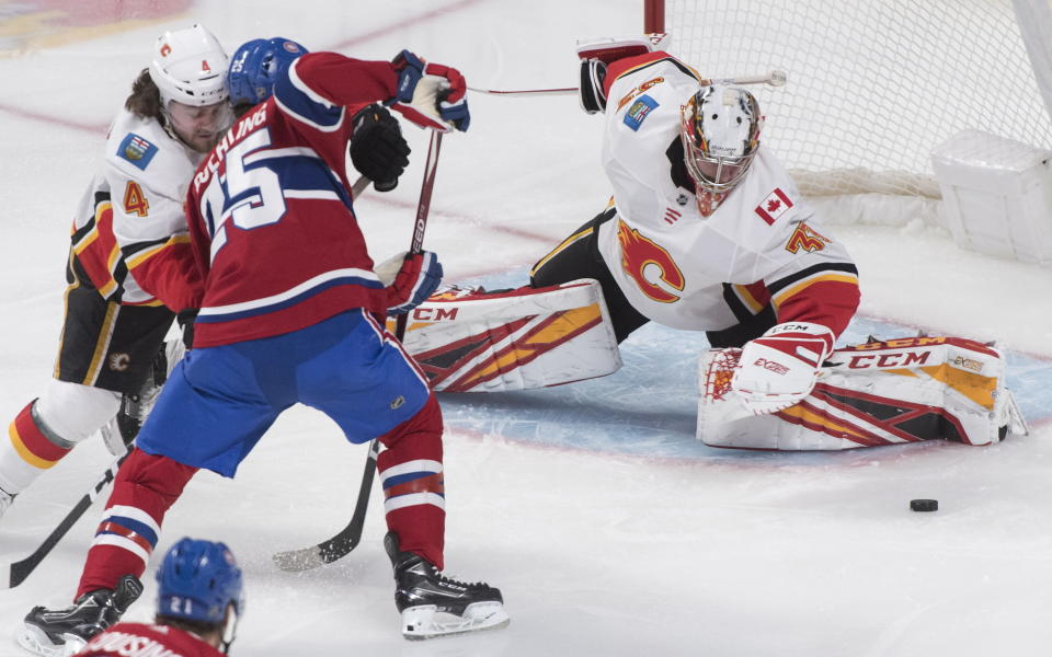 Montreal Canadiens' Ryan Poehling (25) moves in on Calgary Flames goaltender David Rittich as Flames' Rasmus Andersson (4) defends during second period NHL hockey action in Montreal, Monday, Jan. 13, 2020. (Graham Hughes/The Canadian Press via AP)