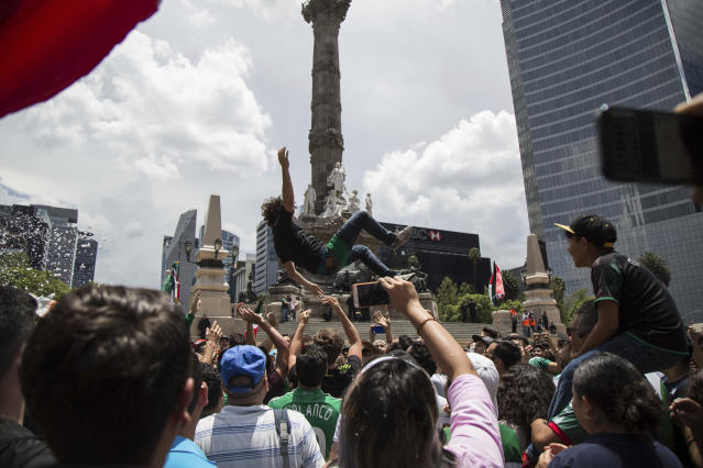 A fan is tossed in the air during the celebration of Mexico's 2018 World Cup win over Germany at the Angel of Independence in Mexico City, Sunday, June 17, 2018. Mexico won it's first match against Germany 1-0. (AP Photo/Anthony Vazquez)