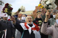People, most of them pensioners, wave bunches of flowers during an opposition rally to protest the official presidential election results in Minsk, Belarus, Monday, Oct. 26, 2020. Factory workers, students and business owners in Belarus have started a general strike, calling for authoritarian President Alexander Lukashenko to resign after more than two months of mass protests triggered by a disputed election. (AP Photo)
