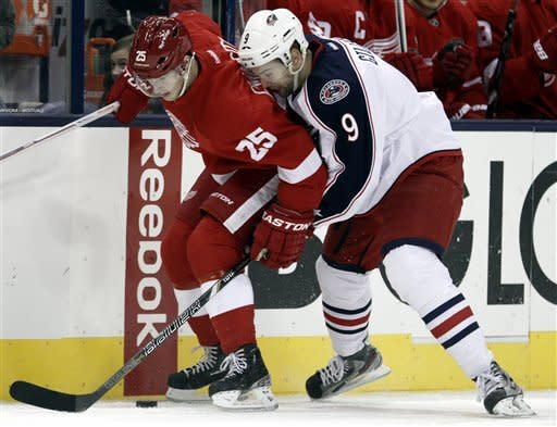 Detroit Red Wings' Cory Emmerton, left, works for the puck against Columbus Blue Jackets' Colton Gillies in the first period of an NHL hockey game in Columbus, Ohio, Saturday, March 9, 2013. (AP Photo/Paul Vernon)