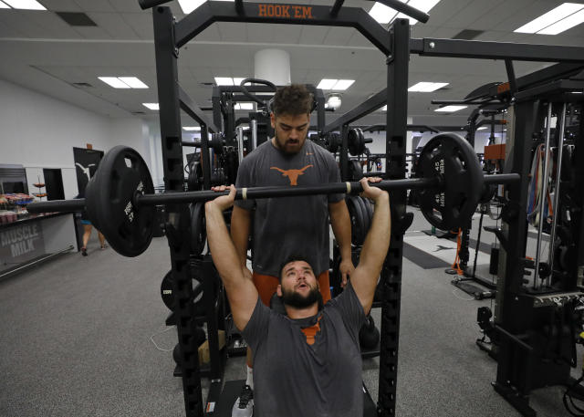 Texas Longhorns' Junior Angilau (top) spots teammate Samuel Cosmi during a morning workout Wednesday Sept. 4, 2019 in Austin, Tx. ( Photo by Edward A. Ornelas )